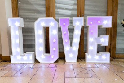 Letters spelling love with white and pink lights