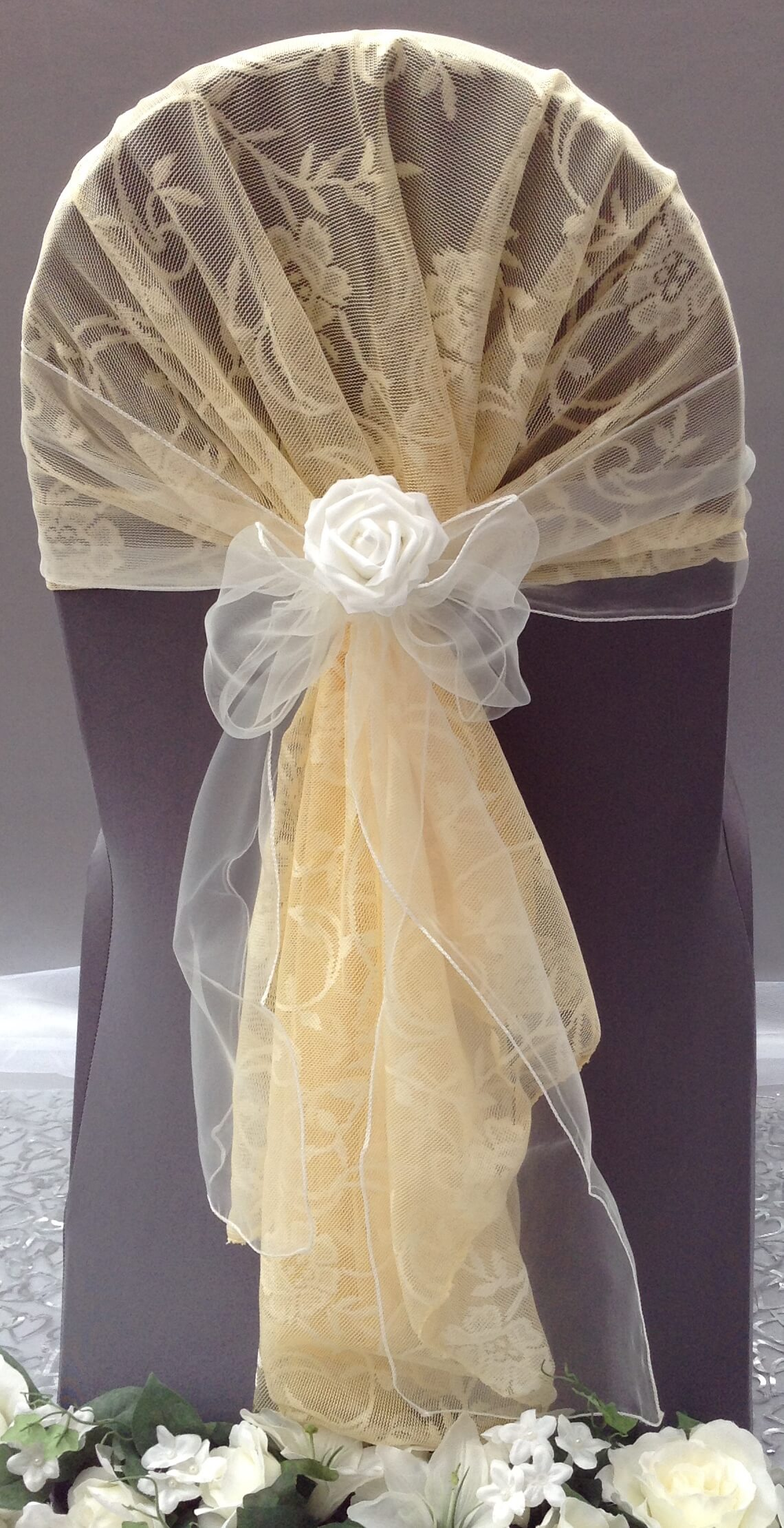 Grey chair cover with gold lace hood with white organza sash with flower
