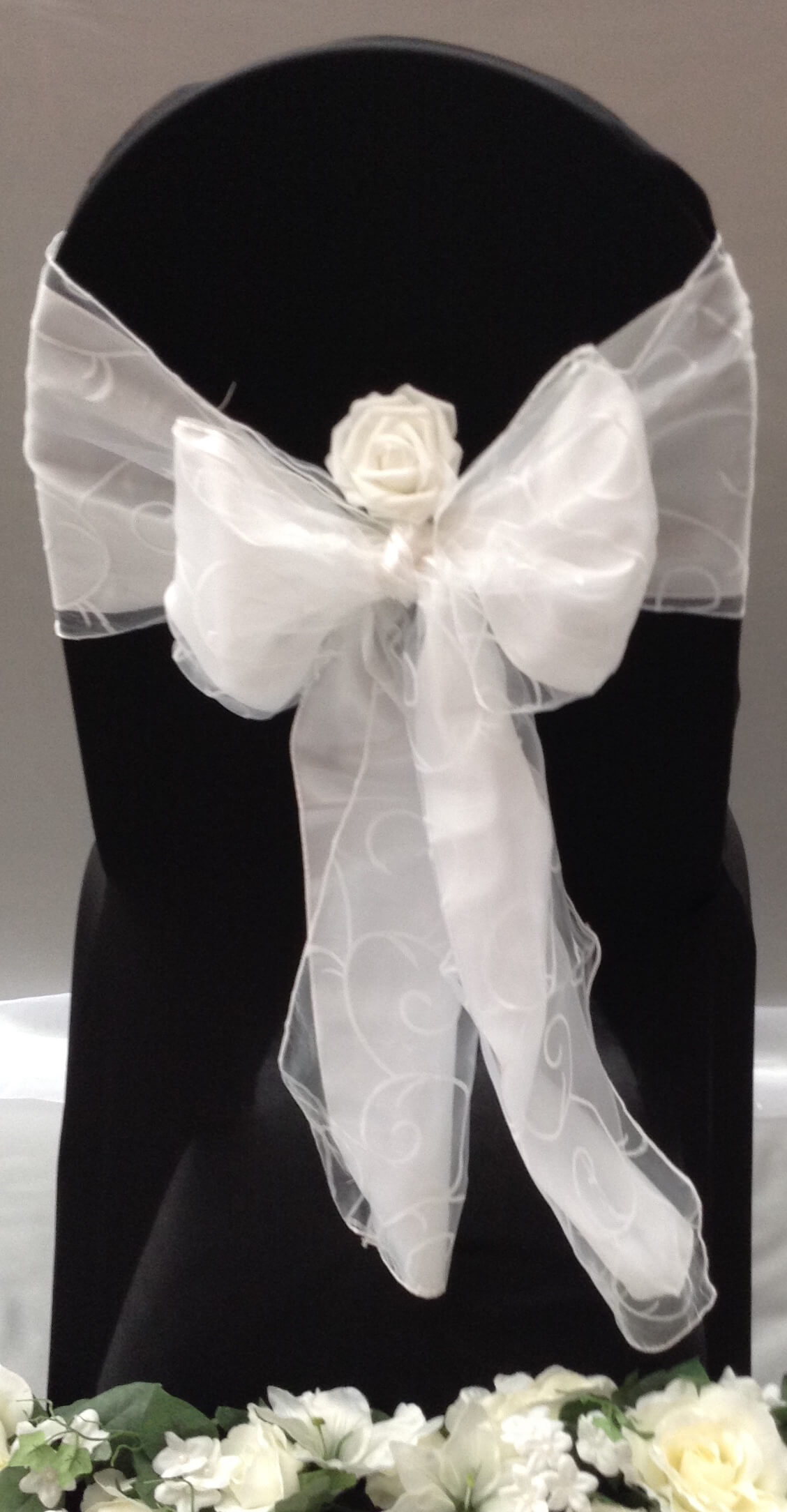 black chair cover with white satin sash and white organza sash