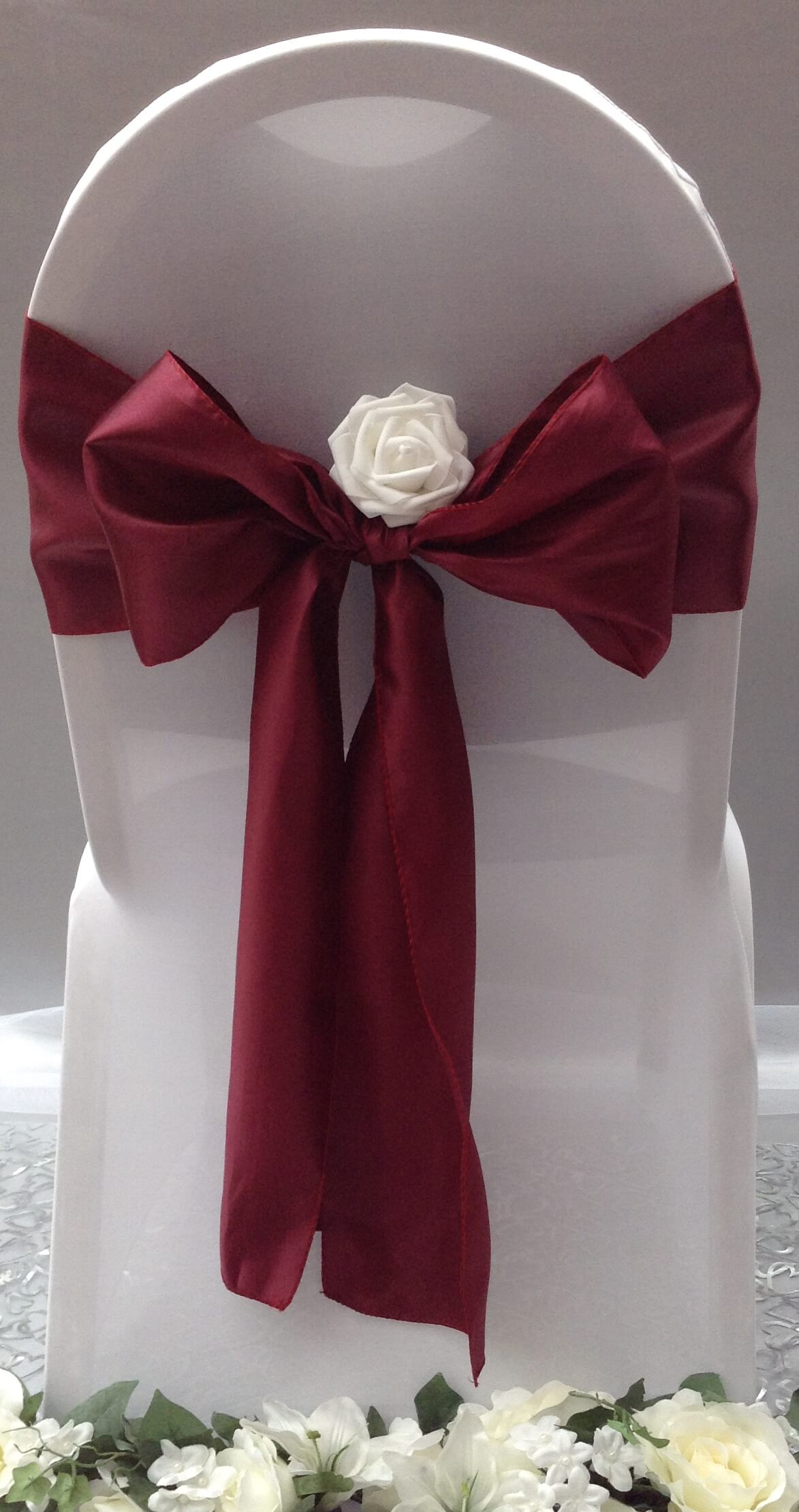 burgundy satin sash with white flower