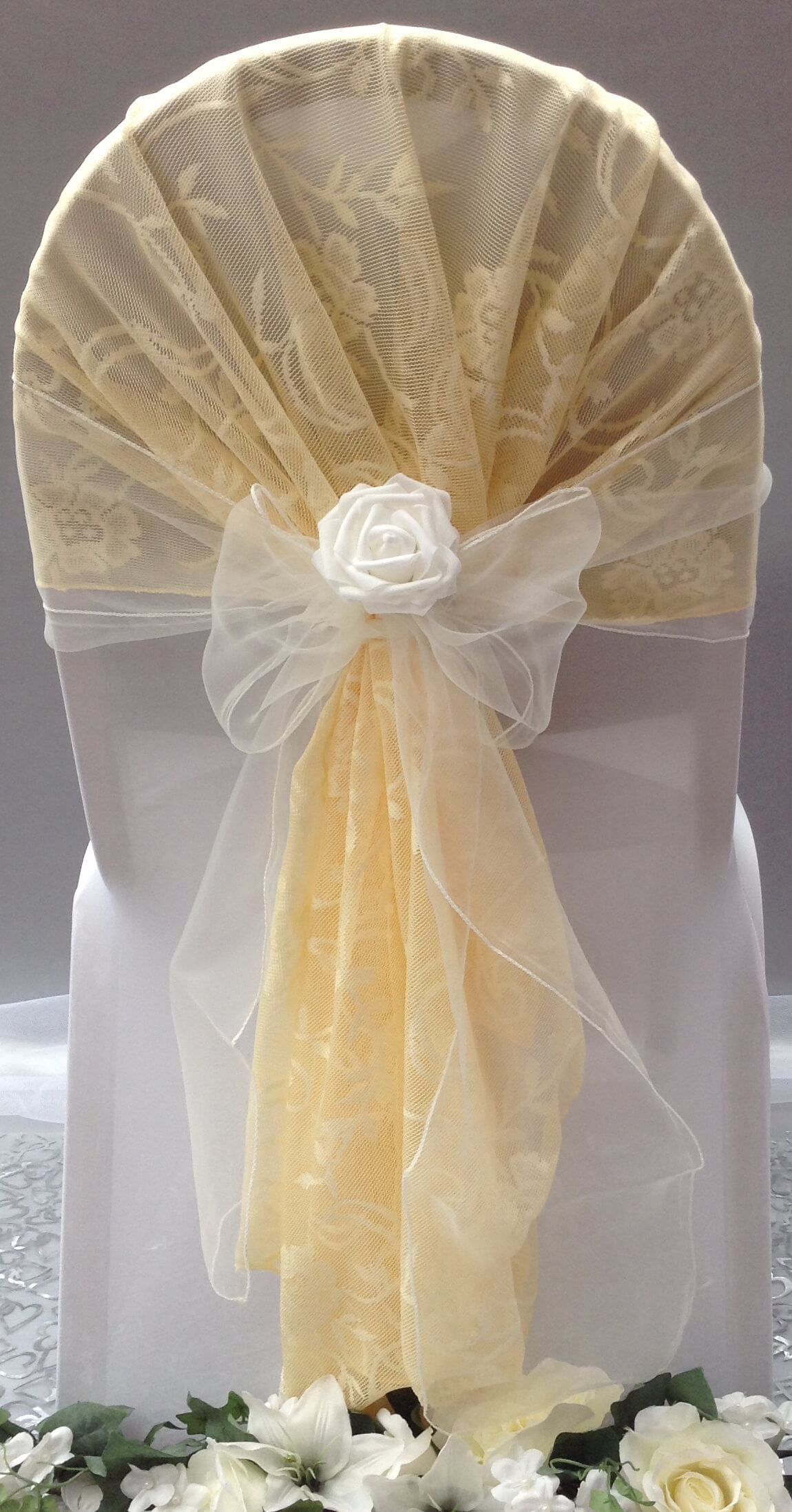 Gold lace hood with with organza sash and flower